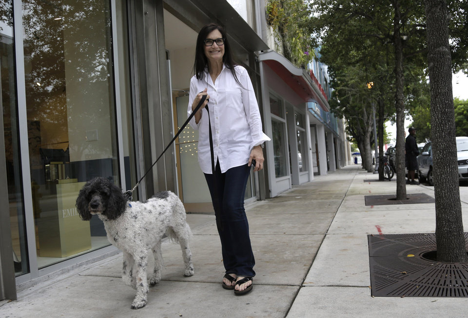 Photo - ADVANCE FOR MONDAY, DEC. 9 AND THEREAFTER - This photo taken Tuesday, Nov. 5, 2013, shows gallery owner Deborah Sponder walking her dog in the Design District neighborhood of Miami. It's not just the wealthiest 1 percent: Fully 20 percent of U.S. adults become rich for parts of their lives, wielding outsized influence on America's economy and politics. And this little-known group may pose the biggest barrier to reducing the nation's income inequality. While the growing numbers of the U.S. poor have been well documented, survey data provided exclusively to The Associated Press detail the flip side of the record income gap: the rise of the