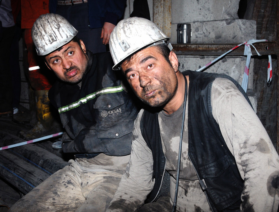 Photo - Two miners look around after being rescued hours after an explosion and fire at a coal mine killed at least 17 miners and left up to 300 workers trapped underground, in Soma, in western Turkey, late Tuesday, May 13, 2014, a Turkish official said. Twenty people were rescued from the mine but one later died in the hospital, Soma administrator Mehmet Bahattin Atci told reporters. The town is 250 kilometers (155 miles) south of Istanbul. The death toll was expected to rise.(AP Photo)