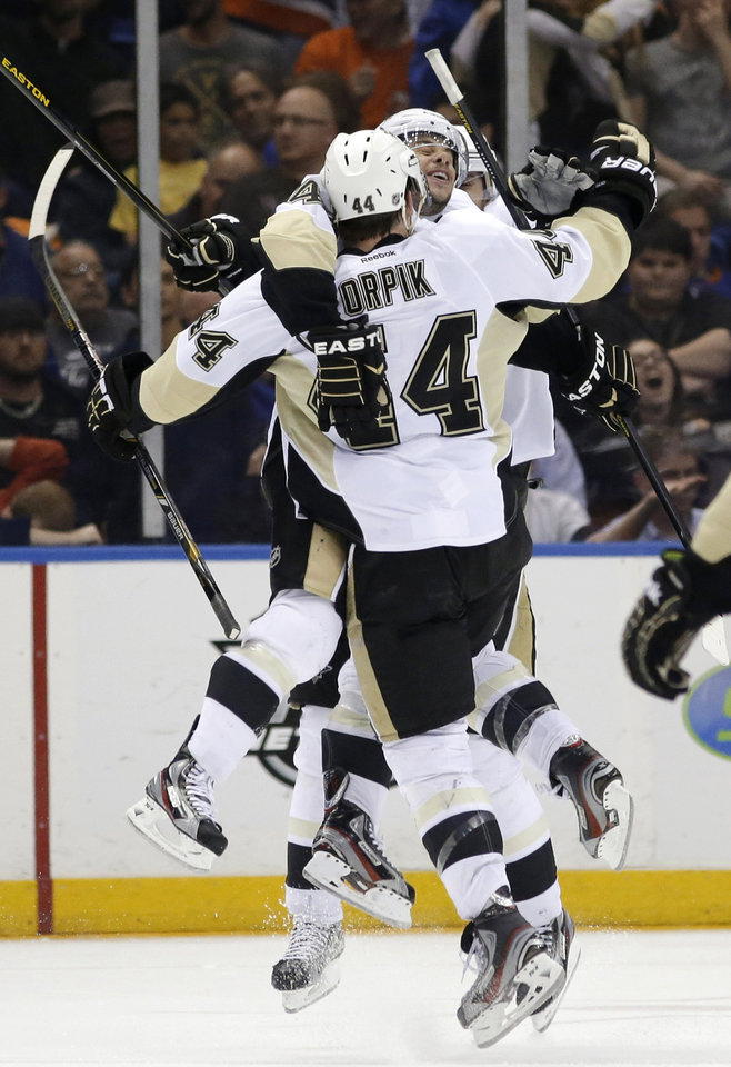Photo - Pittsburgh Penguins center Tyler Kennedy celebrates with defenseman Brooks Orpik (44), who scored the winning goal in overtime of Game 6 of a first-round NHL Stanley Cup playoff hockey series against the New York Islanders in Uniondale, N.Y., Saturday, May 11, 2013. The Penguins won 4-3, and advanced to the Eastern Conference semifinals. (AP Photo/Kathy Willens)