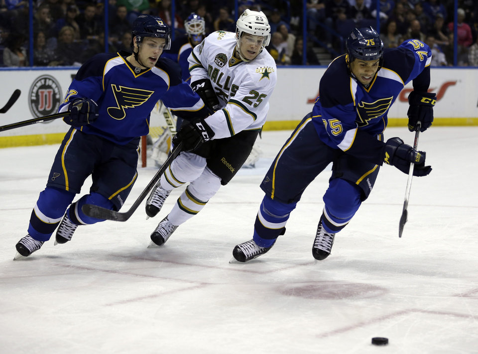 Photo - St. Louis Blues' Ryan Reaves, right, and Vladimir Sobotka, left, of the Czech Republic, and Dallas Stars' Matt Fraser, center, chase after a loose puck during the third period of an NHL hockey game on Friday, April 19, 2013, in St. Louis. The Blues won 2-1. (AP Photo/Jeff Roberson)