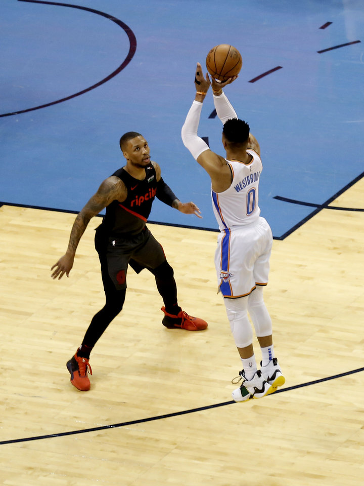 Photo - Oklahoma City's Russell Westbrook (0) shoots a 3-point basket of Portland's Damian Lillard (0) during Game 4 in the first round of the NBA playoffs between the Portland Trail Blazers and the Oklahoma City Thunder at Chesapeake Energy Arena in Oklahoma City, Sunday, April 21, 2019.  Photo by Sarah Phipps, The Oklahoman
