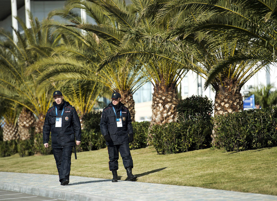 Photo - FILE - In this Feb. 4, 2014 file photo, Russian police officers walk past a row of palm trees while taking in the sunny mild temperatures before the 2014 Sochi Winter Olympics in Sochi, Russia. Sochi hotel guests are walking, unchecked, past unused metal detectors. Security guards are no longer poking around at the pockets and ankles of every single person entering Olympic facilities. Tangerines and bottles of Coke are making it through security barriers that banned them two weeks ago. For all the warnings that security in Sochi would be invasive and aggressive, it's appearing more uneven, and in places almost relaxed.  (AP Photo/The Canadian Press, Nathan Denette, File)
