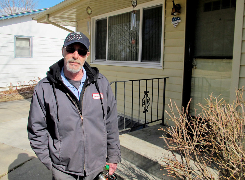 Photo - Robert Atkinson stands outside of the house he shares with his mother in Lincoln, Neb., on Wednesday, March 19, 2014. They face increases in their annual flood insurance premiums due of rate changes from the National Flood Insurance Program, which is $24 billion in debt. he doesn't view the trickling creek near his backyard as a serious threat.