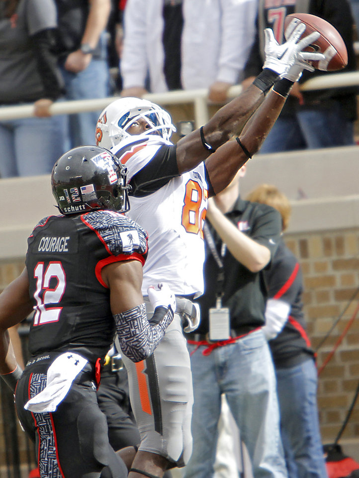 Photo - Oklahoma State Cowboys wide receiver Isaiah Anderson (82) makes a touchdown catch in front of Texas Tech Red Raiders safety D.J. Johnson (12) during the college football game between the Oklahoma State University Cowboys (OSU) and Texas Tech University Red Raiders (TTU) at Jones AT&T Stadium on Saturday, Nov. 12, 2011. in Lubbock, Texas.  Photo by Chris Landsberger, The Oklahoman  ORG XMIT: KOD