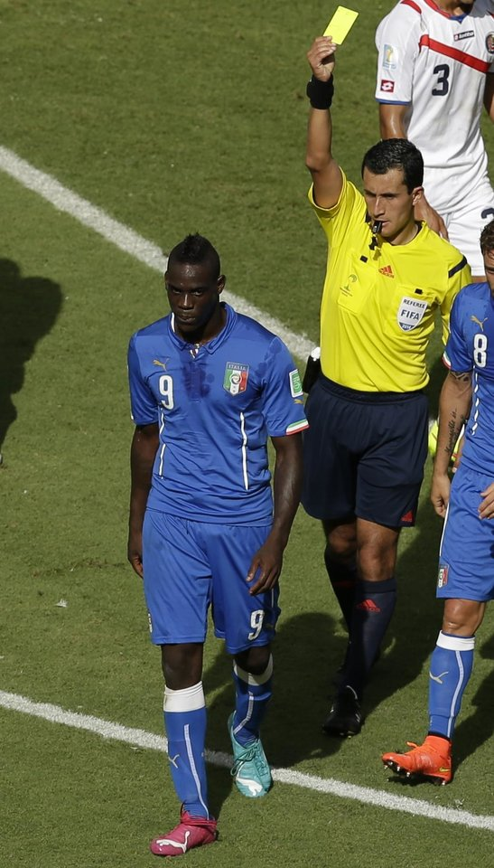 Photo - Italy's Mario Balotelli, left, is booked by referee Enrique Osses from Chile during the group D World Cup soccer match between Italy and Costa Rica at the Arena Pernambuco in Recife, Brazil, Friday, June 20, 2014.  (AP Photo/Hassan Ammar)
