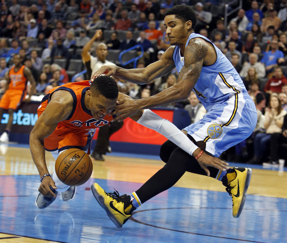 Photo - Oklahoma City's Russell Westbrook (0) and Denver's Gary Harris (14) collide during an NBA basketball game in which the Oklahoma City Thunder defeated the Denver Nuggets 122-112 at Chesapeake Energy Arena on Dec. 27, 2015 in Oklahoma City, Okla. Photo by Steve Sisney, The Oklahoman