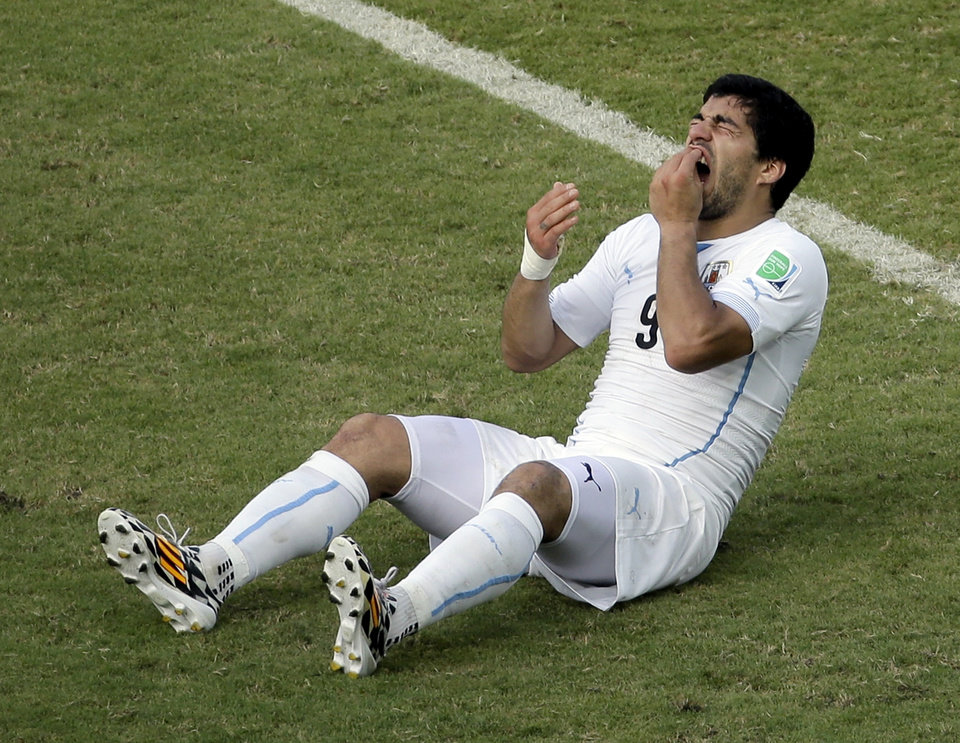 Photo - Uruguay's Luis Suarez (9) holds his teeth after running into Italy's Giorgio Chiellini's shoulder during the group D World Cup soccer match between Italy and Uruguay at the Arena das Dunas in Natal, Brazil, Tuesday, June 24, 2014. (AP Photo/Hassan Ammar)