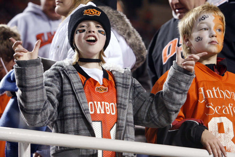 Photo - Kinsey Callen and Noah Rauschenberg, both ten from Tulsa, wear orange and black makeup during the college football game between Oklahoma State University (OSU) and the University of Missouri (MU) at Boone Pickens Stadium in Stillwater, Okla. Saturday, Oct. 17, 2009.  Photo by Steve Sisney, The Oklahoman