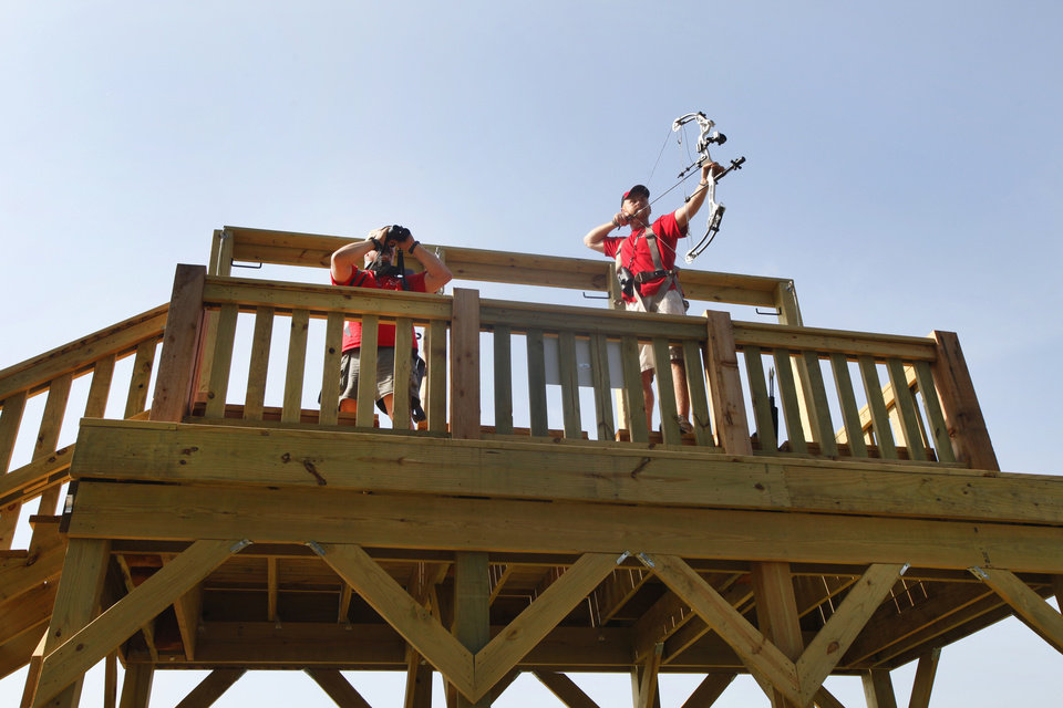 ARCHERY: Jeff Steele, left and Rob Stillwagon aim at a targets from a tower near Crystal Lake in Oklahoma City, Thursday, June 14, 2012. The tower simulates hunting from a tree stand. Photo By Steve Gooch, The Oklahoman