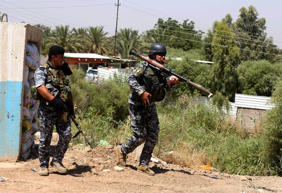 Photo - Iraqi federal policemen patrol in the town of Taji, about 12 miles (20 kilometers) north of Baghdad, Iraq, Thursday, June 26, 2014. The Islamic State of Iraq and the Levant (ISIL) took over the country's second largest city 10 days ago. U.S. Secretary of State John Kerry warned Mideast nations on Wednesday against taking new military action in Iraq that might heighten already-tense sectarian divisions, as reports surfaced that Syria launched airstrikes across the border and Iran has been flying surveillance drones over the neighboring country. (AP Photo/Karim Kadim)