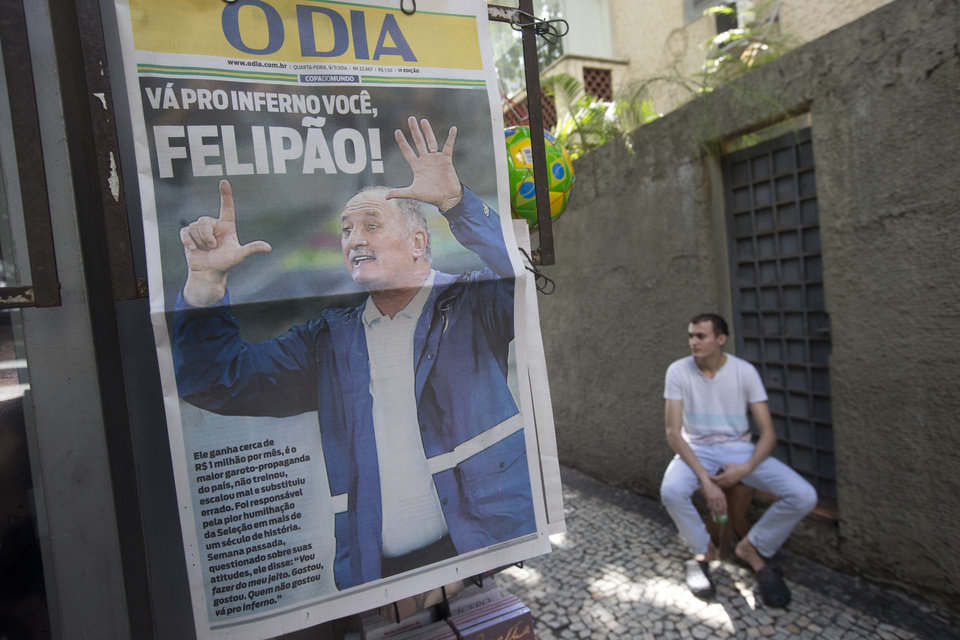 Photo - A man sits on the sidewalk where a newspaper stand displays a paper with a front page that reads in Portuguese