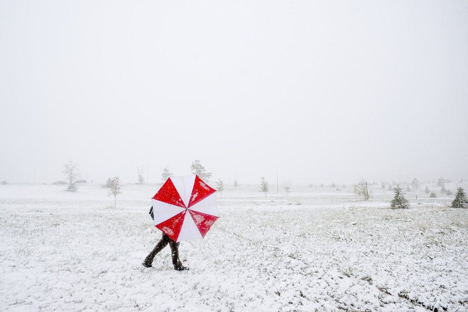 Photo - Pat Blazek shields himself from the snow and wind with an umbrella as he competes in a disc golf tournament Sunday, May 11, 2014, at Aggie Greens in Fort Collins, Colo. Snow is expected to fall through Monday, with highs reaching the sixties later this week. (AP Photo/The Coloradoan, Erin Hull)