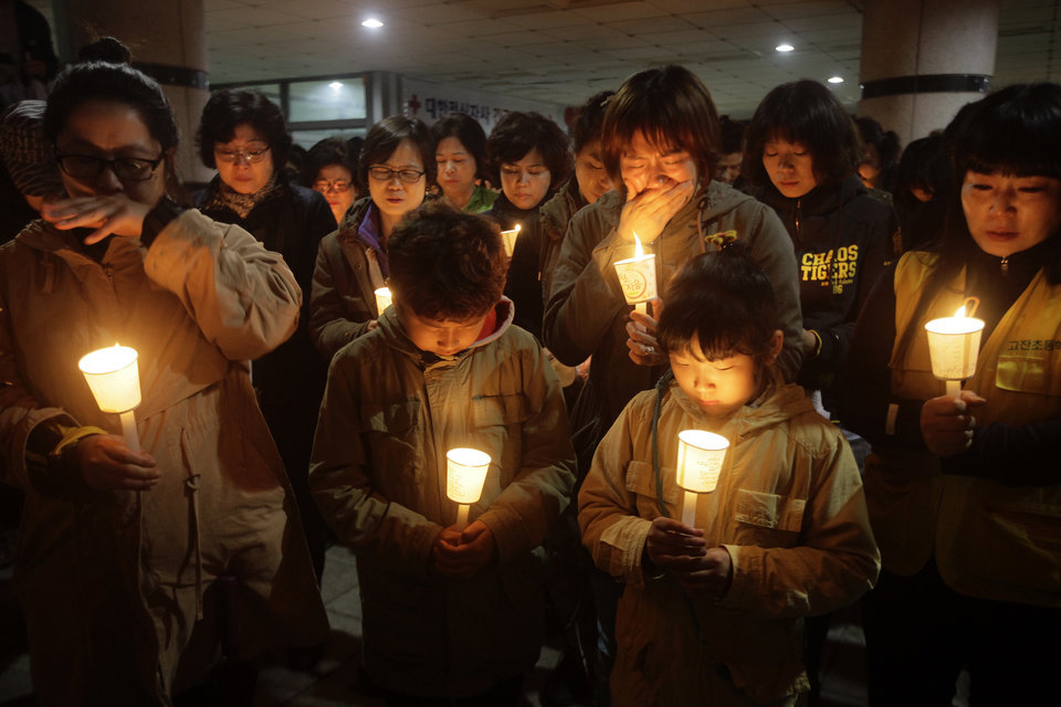 Photo - People gather to pray with candlelights for the missing passengers of a sunken ferry at Danwon High School in Ansan, South Korea, Thursday, April 17, 2014. An immediate evacuation order was not issued for the ferry that sank off South Korea's southern coast, likely with scores of people trapped inside, because officers on the bridge were trying to stabilize the vessel after it started to list amid confusion and chaos, a crew member said Thursday. (AP Photo/Woohae Cho)