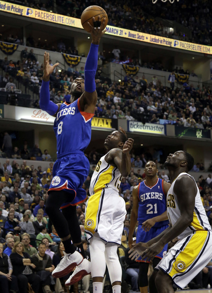 Philadelphia 76ers guard Tony Wroten, left, gets past Indiana Pacers defenders Donald Sloan, second from left and Lance Stephenson, right, during the first half of an NBA basketball game in Indianapolis, Monday, March 17, 2014. (AP Photo/AJ Mast)