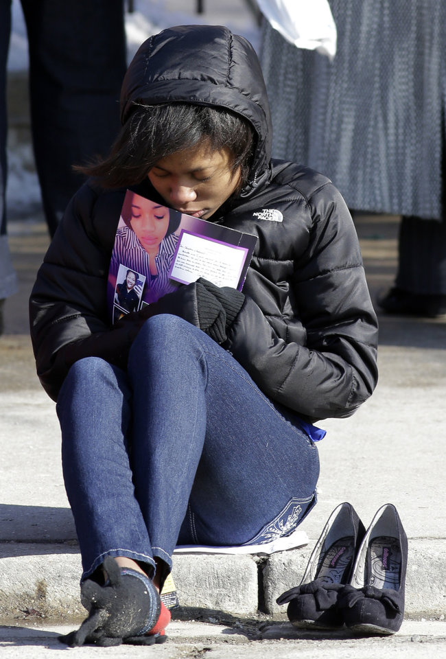 Photo - A mourner reacts as she sits outside the Greater Harvest Missionary Baptist Church during the funeral service of Hadiya Pendleton Saturday, Feb. 9, 2013, in Chicago. Hundreds of mourners and dignitaries including first lady Michelle Obama packed the funeral service Saturday for a Chicago teen whose killing catapulted her into the nation's debate over gun violence. (AP Photo/Nam Y. Huh)