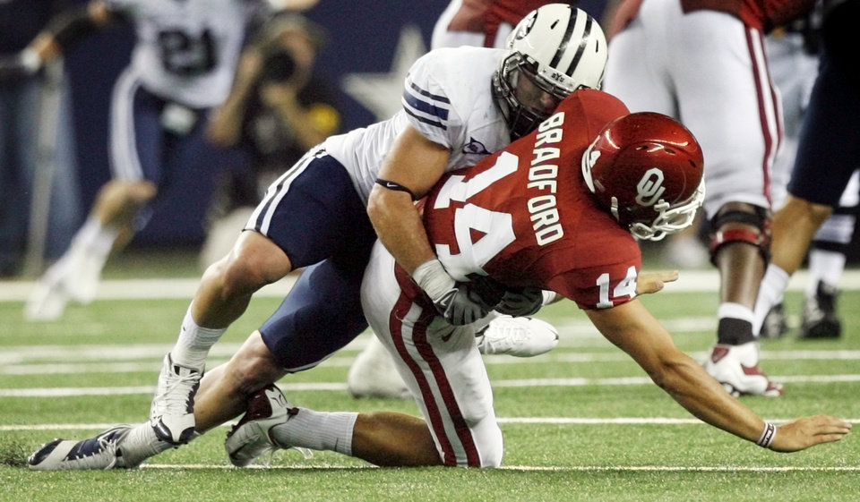 Photo - SHOULDER INJURY / INJURED: BYU's Coleby Clawson (41) drives OU quarterback Sam Bradford (14) into the turf on a play near the end of the second quarter during the college football game between the Brigham Young University Cougars (BYU) and the University of Oklahoma Sooners (OU) at Cowboys Stadium in Arlington, Texas, Saturday, September 5, 2009. Bradford left the field after the play. By Nate Billings, The Oklahoman ORG XMIT: KOD