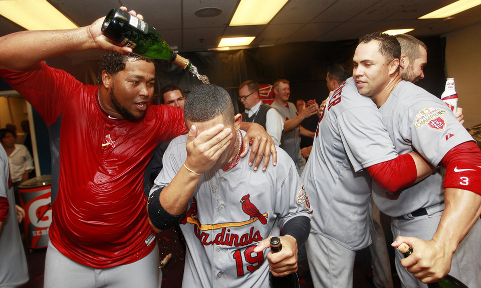 Photo -   From left to right, St. Louis Cardinals' Victor Marte, Jon Jay, Chris Carpenter and Carlos Beltran celebrate in the locker room after defeating the Atlanta Braves 6-3 in the National League wild card playoff baseball game on Friday, Oct. 5, 2012, in Atlanta. (AP Photo/John Bazemore)