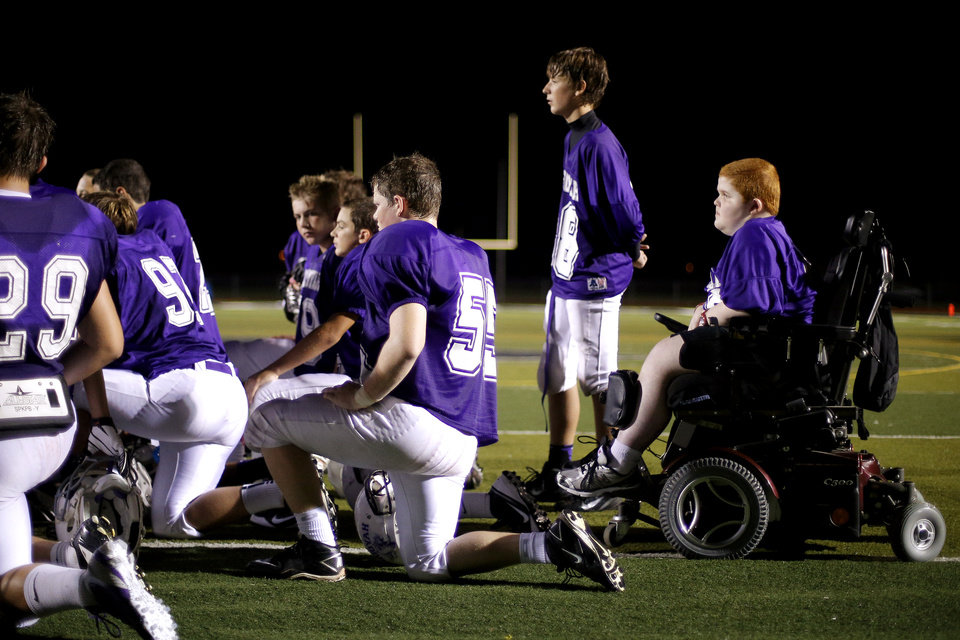 Photo - Keegan Erbst listens tot he coaches with the Sequoyah Middle School football team after a game, Thursday, September 27, 2012. Keegan, who has muscular dystrophy and is confined to a wheelchair, got involved with the team after players Lucas Coker, Colton James, and Parker Tumleson, pushed suggested it to the coach.  Photo by Bryan Terry, The Oklahoman