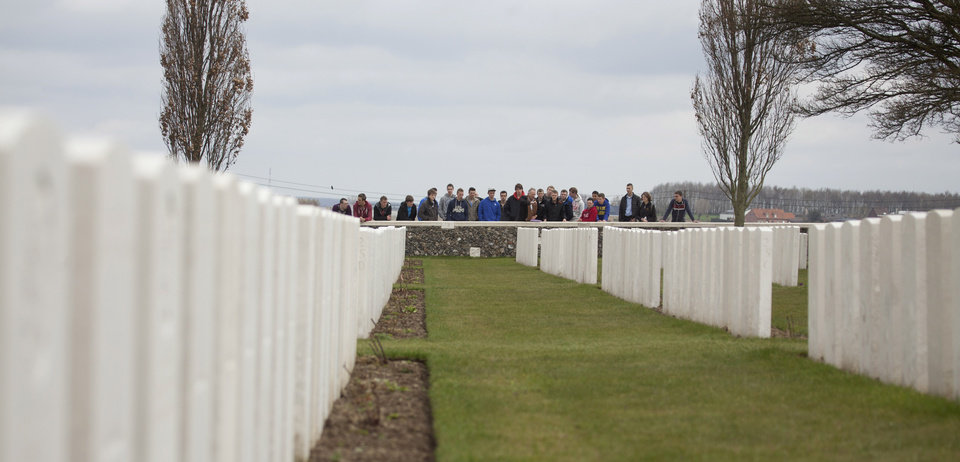 Photo - A group of school children look over a stone fence toward a row of WWI graves at Tyne Cot cemetery in Zonnebeke, Belgium on Monday, April 15, 2013. With nearly 12,000 graves the cemetery is the largest Commonwealth war cemetery in the world in terms of burials. Currently renovation work is being done on the cemetery in preparation for centenary events which begin in 2014. (AP Photo/Virginia Mayo)