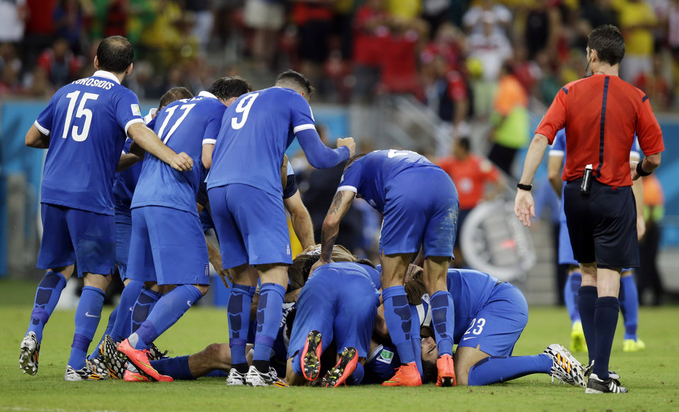 Photo - Greece's Sokratis Papastathopoulos, bottom, reacts with teammates after scoring a goal during the World Cup round of 16 soccer match between Costa Rica and Greece at the Arena Pernambuco in Recife, Brazil, Sunday, June 29, 2014. (AP Photo/Andrew Medichini)