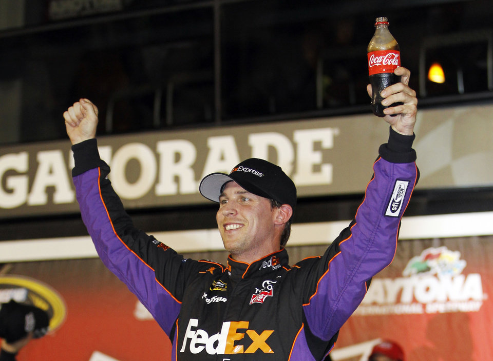Photo - Denny Hamlin celebrates in Victory Lane after winning the second of two NASCAR Sprint Cup series qualifying auto races at Daytona International Speedway in Daytona Beach, Fla., Thursday, Feb. 20, 2014. (AP Photo/Terry Renna)