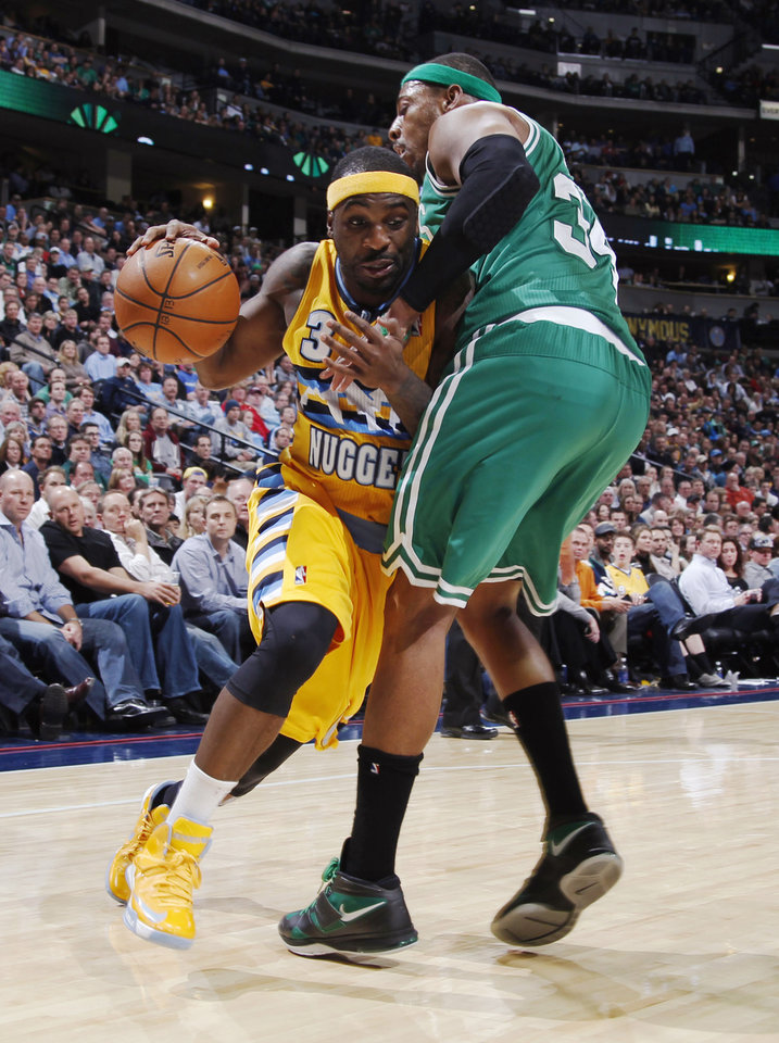 Photo - Denver Nuggets guard Ty Lawson, left, is fouled while driving to the basket by Boston Celtics forward Paul Pierce in the fourth quarter of the Nuggets' 97-90 victory in an NBA basketball game in Denver on Tuesday, Feb. 19, 2013. (AP Photo/David Zalubowski)