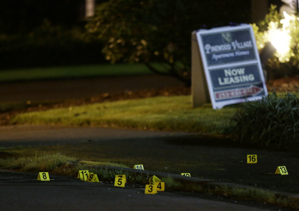 Photo - Evidence markers are shown near a leasing sign at the scene of an overnight shooting that left five people dead, Monday, April 22, 2013, at the Pinewood Village apartment complex in Federal Way, Wash. (AP Photo/Ted S. Warren)