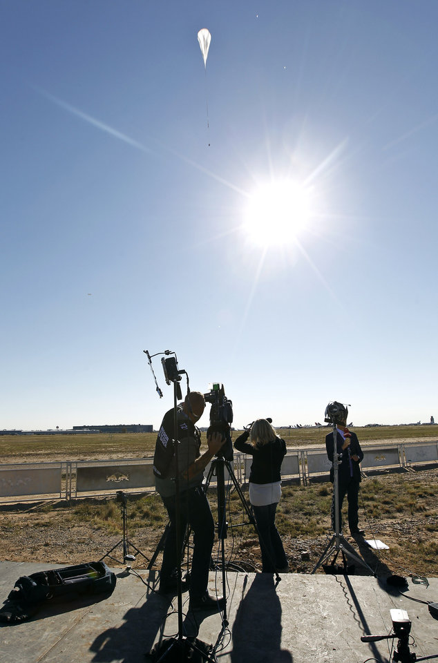 A television crew films the capsule and attached helium balloon, at top of frame, carrying Felix Baumgartner lifting off as he attempts to break the speed of sound with his own body by jumping from a space capsule lifted by a helium balloon, Sunday, Oct. 14, 2012, in Roswell, N.M.  Baumgartner plans to jump from an altitude of 120,000 feet, an altitude chosen to enable him to achieve Mach 1 in free fall, which would deliver scientific data to the aerospace community about human survival from high altitudes.(AP Photo/Ross D. Franklin) ORG XMIT: NMRF109