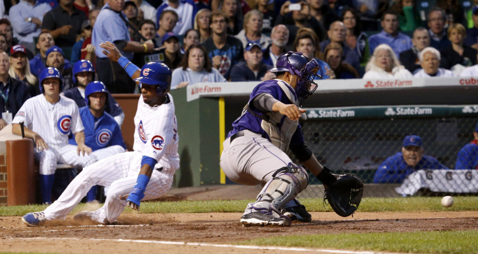 Photo - Chicago Cubs' Arismendy Alcantara, left, scores past Colorado Rockies catcher Wilin Rosario on a sacrifice fly by Justin Ruggiano and the throw from right fielder Carlos Gonzalez, during the fourth inning of a baseball game Monday, July 28, 2014, in Chicago. (AP Photo/Charles Rex Arbogast)