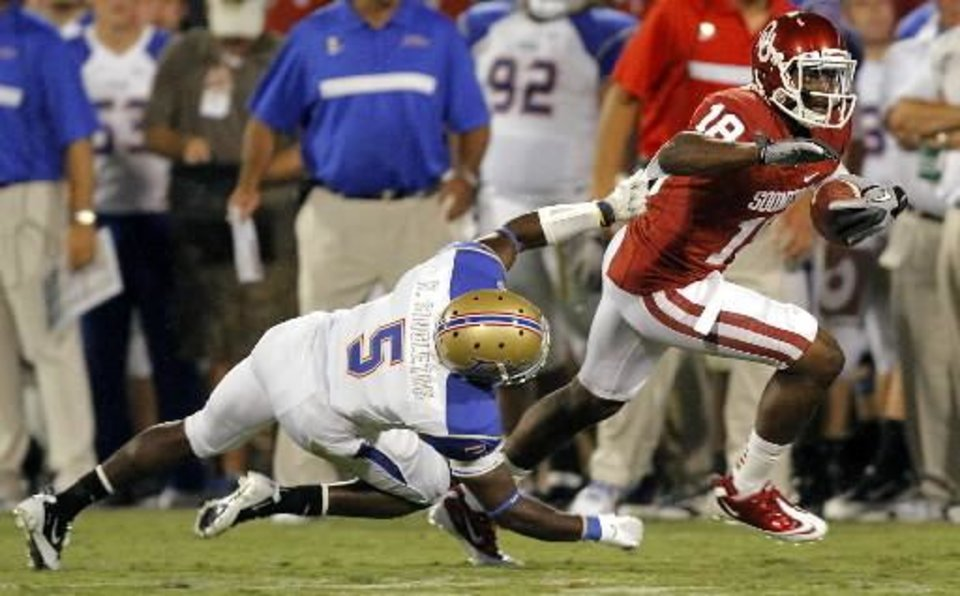 Photo - Oklahoma's Kameel Jackson (18) gets past Tulsa's Reid Singleton (5) during the college football game between the University of Oklahoma Sooners ( OU) and the Tulsa University Hurricanes (TU) at the Gaylord Family-Memorial Stadium on Saturday, Sept. 3, 2011, in Norman, Okla. Photo by Chris Landsberger, The Oklahoman ORG XMIT: KOD