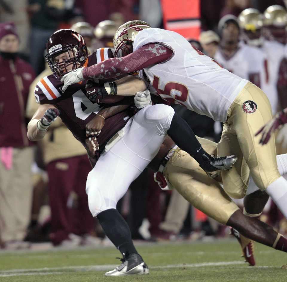 Photo -   Virginia Tech fullback Joey Phillips (45) gains a few yards against Florida State defensive end Bjoern Werner (95) during the first half of an NCAA college football game in Blacksburg, Va., Thursday, Nov. 8, 2012. (AP Photo/Steve Helber)