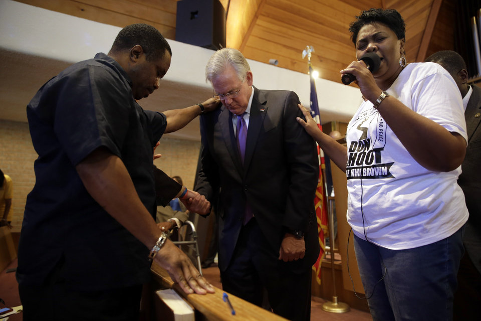Photo - Missouri Gov. Jay Nixon, center, prays during a meeting of clergy and community members held to discuss law enforcement's response to demonstrations over the killing of Michael Brown, Thursday, Aug. 14, 2014, in Florissant, Mo. Nixon says
