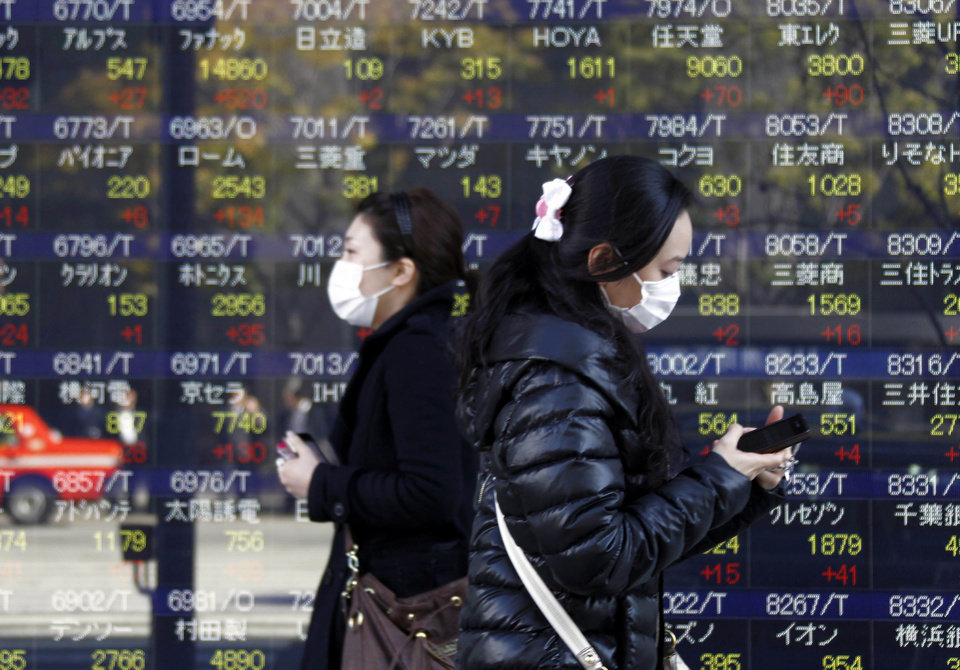 Photo - People walk by an electronic stock board of a securities firm in Tokyo, Thursday, Dec. 13, 2012. Asian stock markets rose Thursday with the help of Japan's Nikkei 225, which was propelled higher by a weakening yen. (AP Photo/Koji Sasahara)