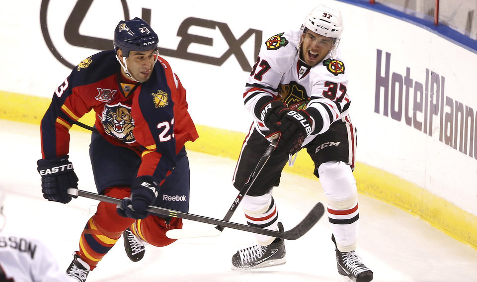 Photo - Florida Panthers' Scott Gomez (23) and Chicago Blackhawks' Brandon Pirri (37) chase the puck during the first period of an NHL hockey game in Sunrise, Fla., Tuesday, Oct. 22, 2013 (AP Photo/J Pat Carter)