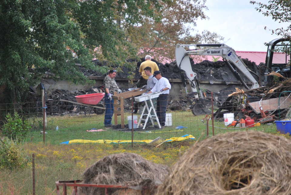 Photo -   Workers are still on the job Thursday, Sept. 27, 2012, near Shelbyville, Tenn., at the site of a house fire that where an elderly couple and two young children lived. Authorities were searching the debris for the remains of the two missing children, 9-year-old Chloie Leverette and 7-year-old Gage Daniel. The two children were initially believed to have perished in the intense fire, which firefighters battled overnight Sunday and early Monday. (AP Photo/Kristin M. Hall)