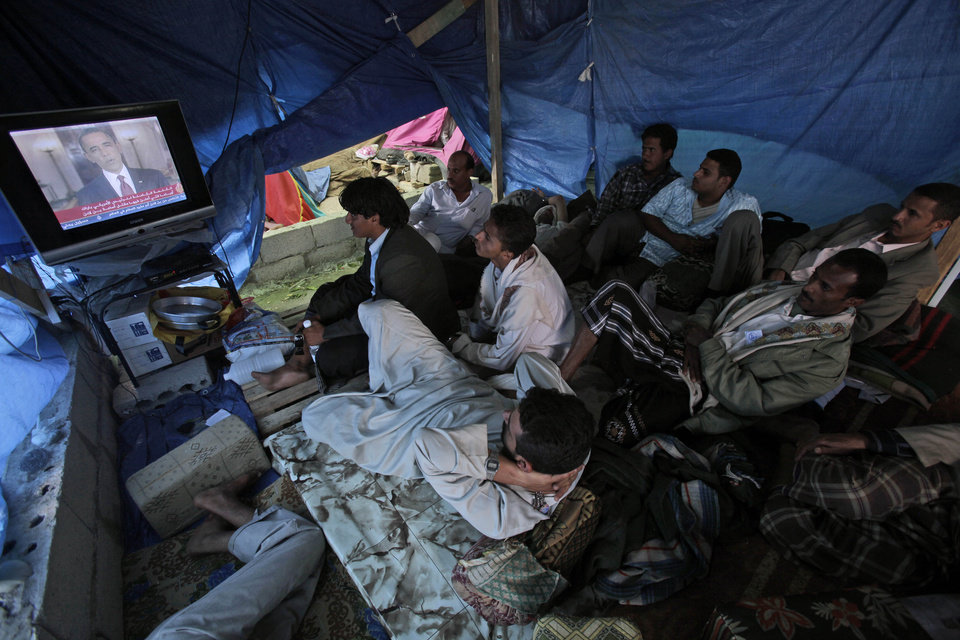 Photo - Anti-government protestors watch a TV broadcasting President Barack Obama statement on the death of Al-Qaida leader Osama bin Laden, in a tent at the site of a demonstration demanding the resignation of Yemeni President Ali Abdullah Saleh, in Sanaa,Yemen, Monday, May 2, 2011. Osama bin Laden, the glowering mastermind behind the Sept. 11, 2001, terror attacks that killed thousands of people, was slain in his luxury hideout in Pakistan early Monday in a firefight with U.S. forces, ending a manhunt that spanned a frustrating decade. (AP Photo/Muhammed Muheisen)