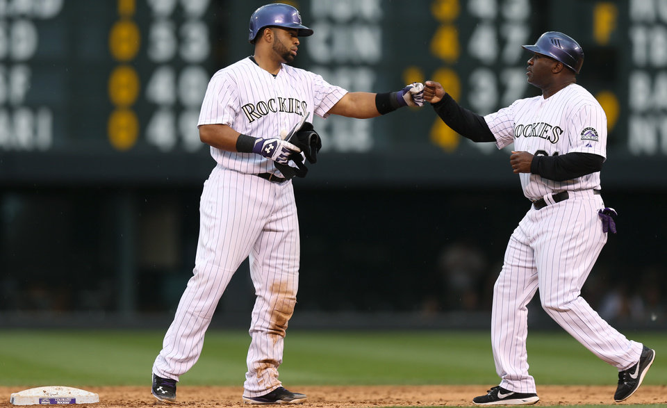 Photo - Colorado Rockies' Wilin Rosario, left, is congratulated by first base coach Eric Young after hitting a double to drive in two runs against the Milwaukee Brewers in the third inning of a baseball game in Denver, Sunday, June 22, 2014. (AP Photo/David Zalubowski)