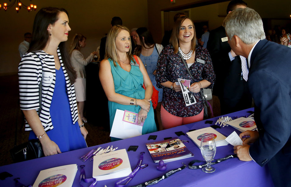 Photo -  Jennifer Davis, a teacher at Will Rogers Elementary School, left, beside Heartland Middle School teachers, Dana Williams, and Haylee Frazier, at right, gather information at a booth during the Edmond Area Chamber of Commerce new teacher reception. [STAFF PHOTO BY BRYAN TERRY, THE OKLAHOMAN]