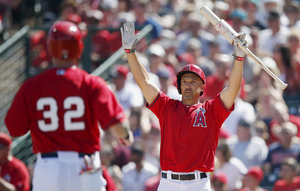 Photo - Los Angeles Angels' Raul Ibanez, right, signals runner Josh Hamilton (32) not to slide as Hamilton comes in to score against the Kansas City Royals during the second inning of a spring training baseball game on Friday, March 21, 2014, in Tempe, Ariz. (AP Photo/Ross D. Franklin)