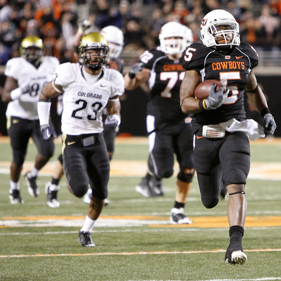 Photo - Keith Toston runs past Colorado's Jalil Brown in his way to a touchdown in the third quarter of the college football game between Oklahoma State University (OSU) and the University of Colorado (CU) at Boone Pickens Stadium in Stillwater, Okla., Thursday, Nov. 19, 2009. Photo by Bryan Terry, The Oklahoman