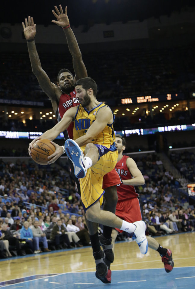 New Orleans point guard Greivis Vasquez (21) passes the ball around Toronto power forward Amir Johnson (15) during the fourth quarter of an NBA basketball game at the New Orleans Arena in New Orleans, Friday, Dec. 28, 2012. (AP Photo/Dave Martin)