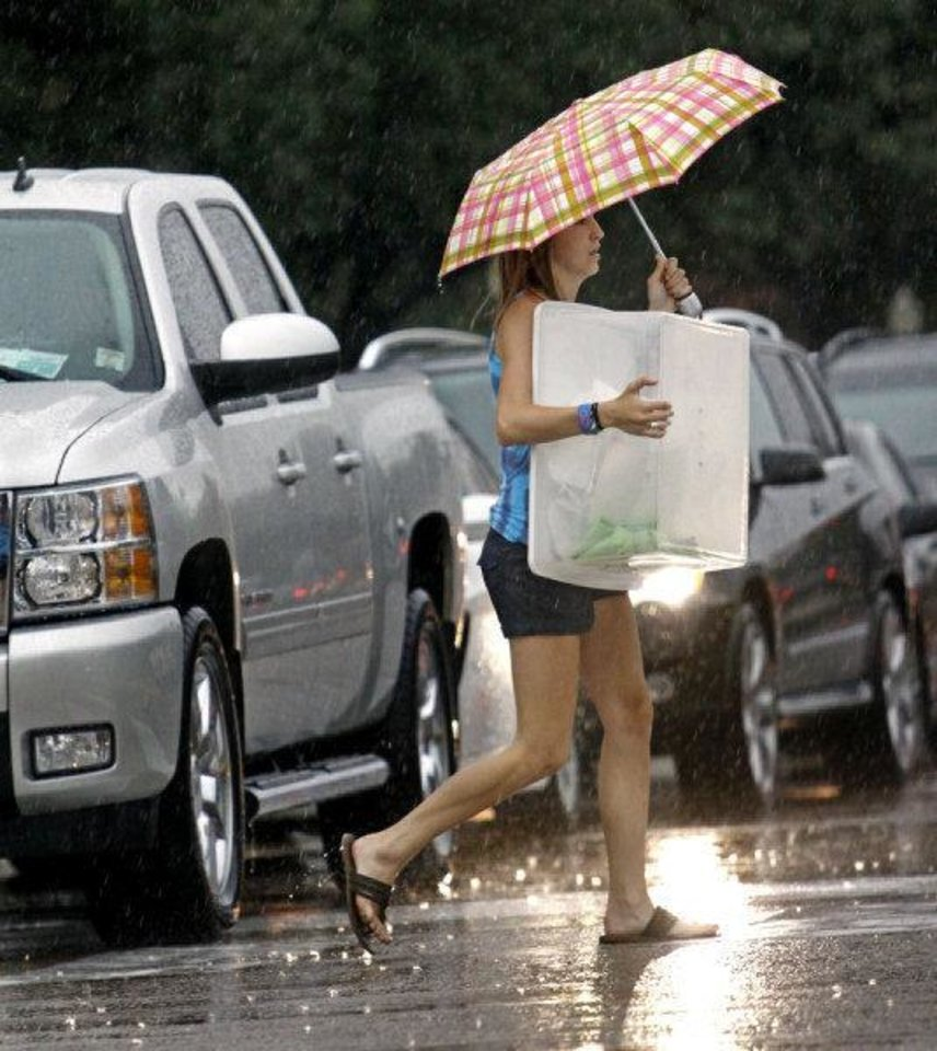 Photo - Gwendolyn Devonshire helps a friend  move into a dormitory at the University of Oklahoma as heavy rain falls on Thursday, August 11, 2011, in Norman, Okla.  Photo by Steve Sisney, The Oklahoman ORG XMIT: KOD