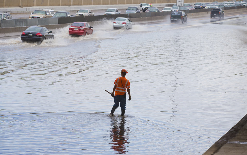 An ADOT worker unplugs a drain on the U.S. 60 after heavy rains blocked all but one lane under the Kyrene overpass in Tempe, Ariz., Sunday, July 21, 2013. (AP Photo/The Arizona Republic, Michael Chow)