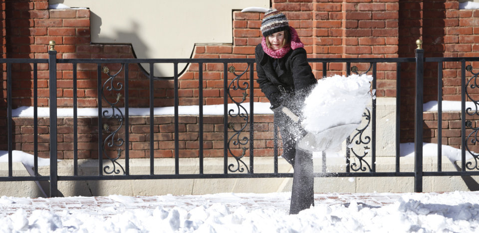 Photo - Michelle Ladd shovels snow in downtown Guthrie, February  3 , 2011. Photo by Steve Gooch, The Oklahoman