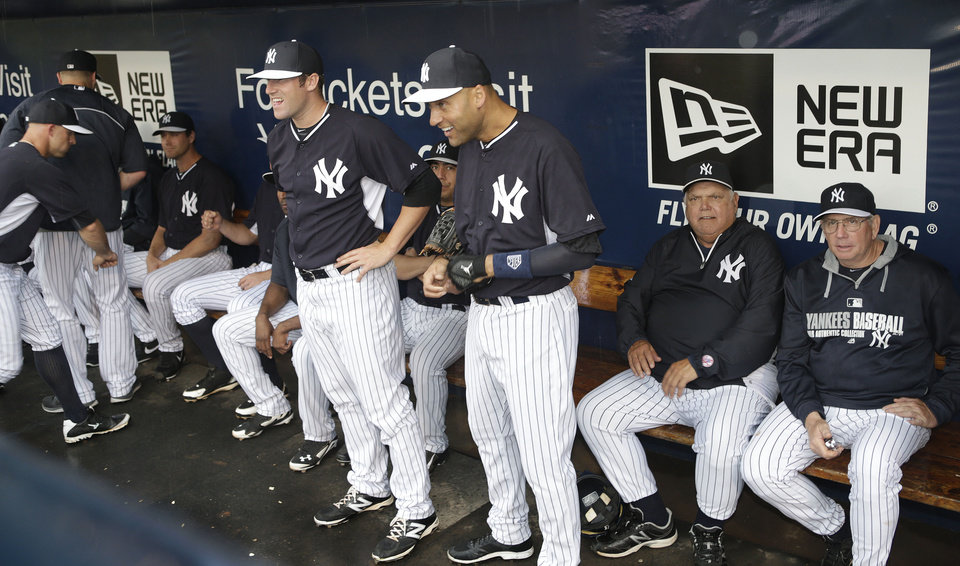 Photo - New York Yankees shortstop Derek Jeter, center, teammates and coaches wait out a rain delay in the dugout before the Yankees final spring exhibition baseball game against the Miami Marlins was canceled due to rain in Tampa, Fla., Saturday, March 29, 2014. (AP Photo/Kathy Willens)