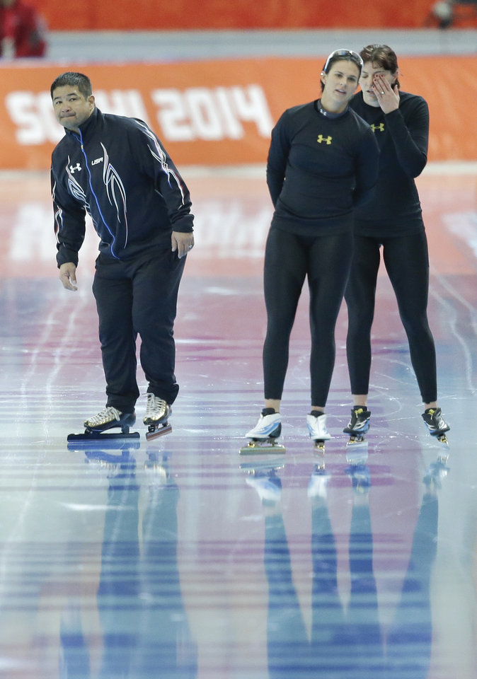 Photo - Coach Ryan Shimabukuro of the U.S., left,  examines the trail of the skates of U.S. speed skaters Heather Richardson, right, and Brittany Bowe, center, during a short practice at the Adler Arena Skating Center at the 2014 Winter Olympics, Saturday, Feb. 15, 2014, in Sochi, Russia. U.S. skaters are looking to bounce back from an awful start to their Olympics by slipping back into their old suits that should have been made obsolete by new high-tech gear. (AP Photo/Patrick Semansky)