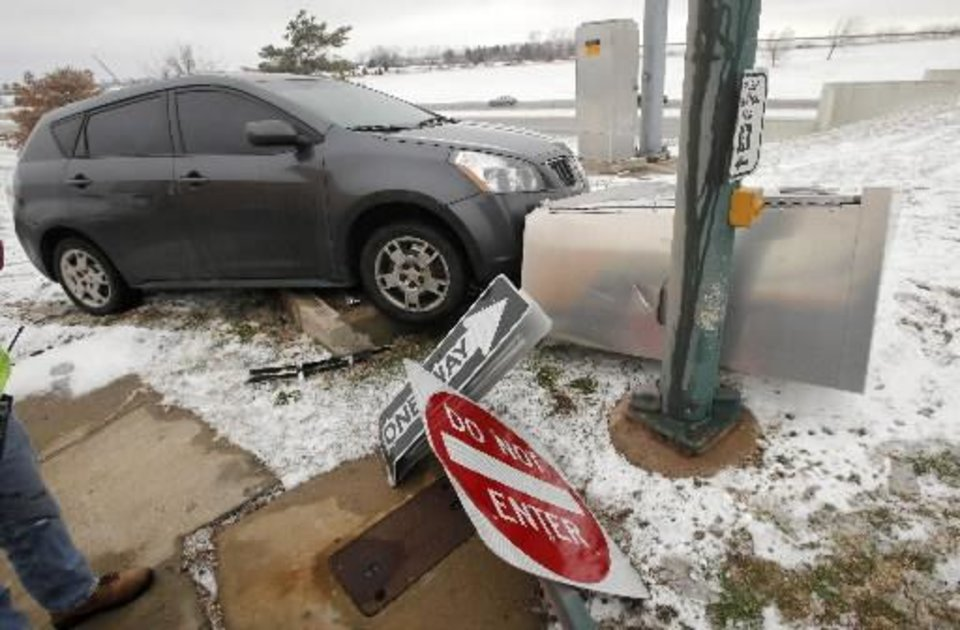 Photo - A driver lost control on the ice and snow and ran over the traffic signal control box at the end of the north bound exit ramp from the Lake Hefner Parkway at Hefner Road in Oklahoma City Monday, Feb. 13, 2012. The wreck resulted in long traffic delays at the intersections on Hefner Road when the lights stopped working. Photo by Paul B. Southerland