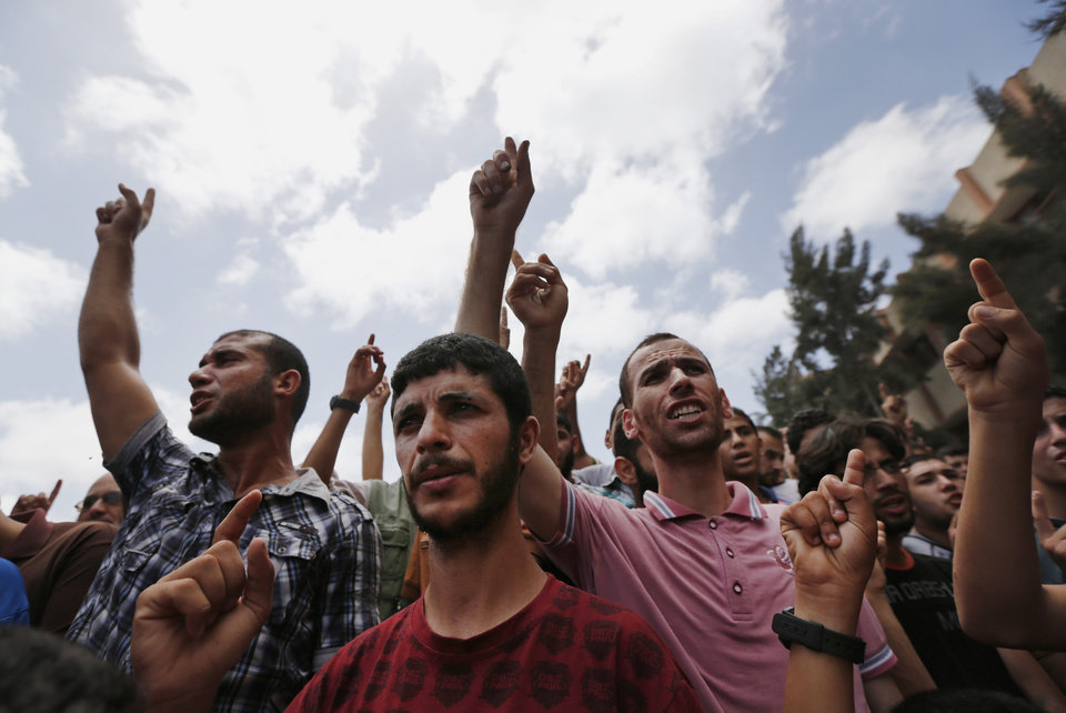 Photo - Palestinian mourners chant slogans during a funeral procession of a member of the al-Batsh family who were killed in Saturday's Israeli airstrike, during a funeral procession in Gaza City on Sunday, July 13, 2014. The strike hit the home of Gaza police chief Taysir al-Batsh and damaged a nearby mosque as evening prayers ended Saturday, killing at least 18 people, wounding 50 and leaving some people believed to be trapped under the rubble, said Palestinian Health Ministry official Ashraf al-Kidra. (AP Photo/Lefteris Pitarakis)