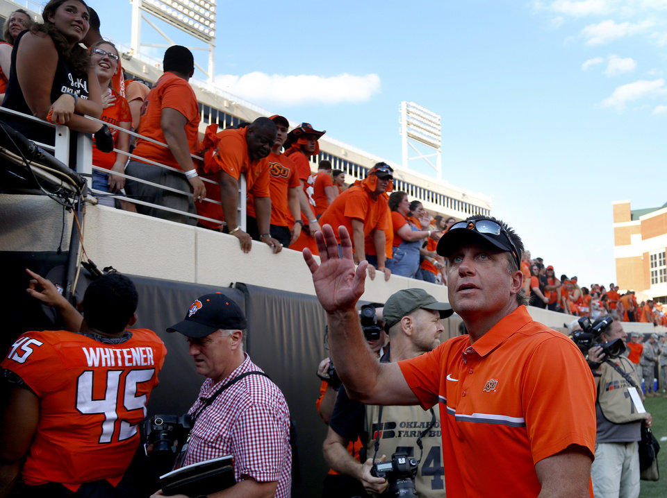 Photo - Coach Mike Gundy waves as he leaves the field during the college football game between the Oklahoma State Cowboys (OSU) and the Southeastern Louisiana Lions at Boone Pickens Stadium in Stillwater, Okla., Saturday, Sept. 12, 2015. Photo by Sarah Phipps, The Oklahoman