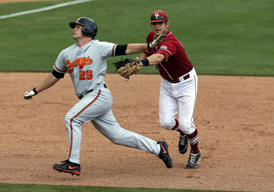 Photo - Oklahoma State's Zach Fish is tagged out by Oklahoma's Garrett Carey during the Bedlam baseball game between the University of Oklahoma and Oklahoma State University at the Chickasaw Bricktown Ballpark in Oklahoma CIty, Saturday, May 11, 2013. Photo by Sarah Phipps, The Oklahoman